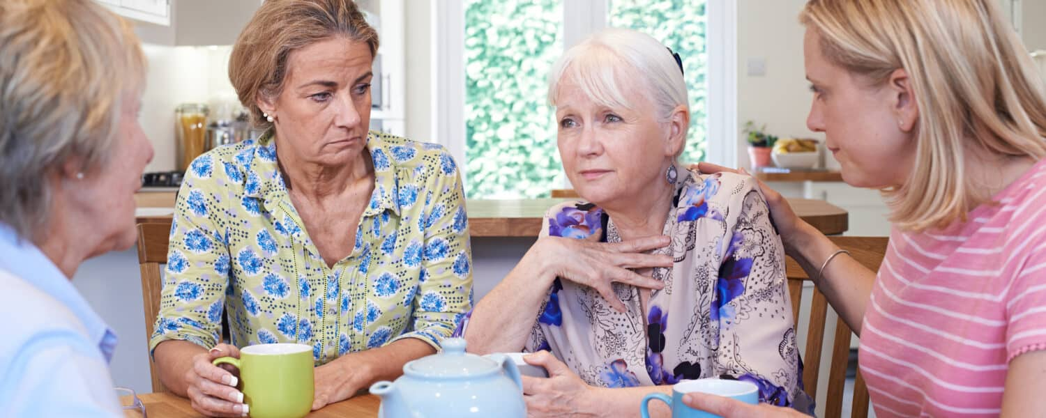 Woman around a table discussing quality and affordable hearing aids