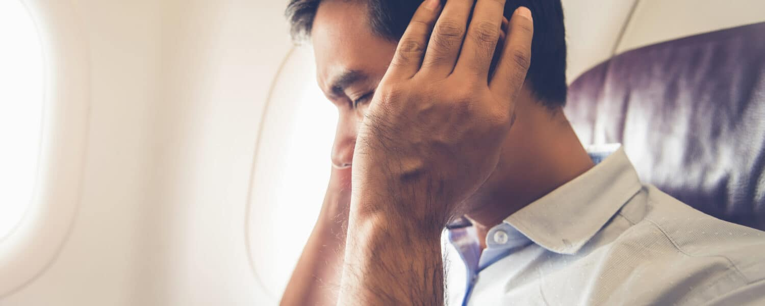 Man sitting on an airplane with his hands over his ears, he possibly has clogged ears or hearing loss and is uncomfortable