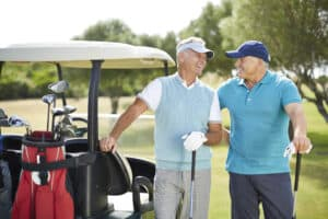Two men wearing premium hearing aids outside while playing golf