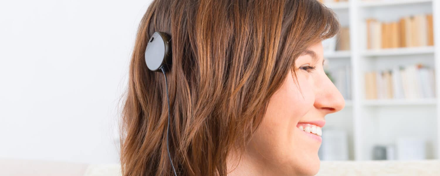 A smiling woman wearing a cochlear implant after taking the best online hearing test