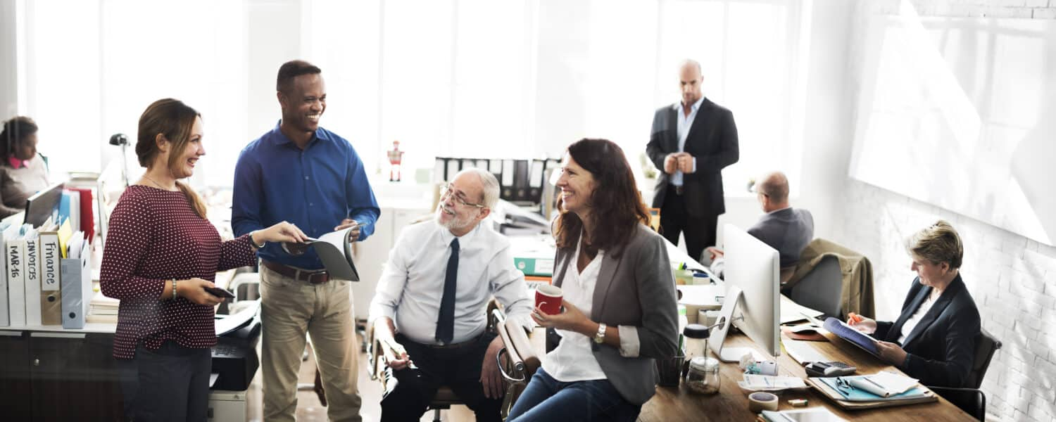 A busy workplace environment with multiple people working and standing around talking to eachother. The perfect example of how hearing loss and workplace are linked to each other.