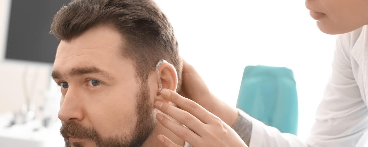 Man being fitted with a hearing aid by a woman hearing aid expert due to him having hearing loss