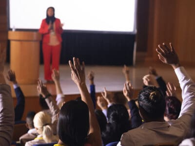 A auditorium full of people listening to a woman speak, some with hearing aids and radio frequencies connecting their hearing aids to the speakers microphone