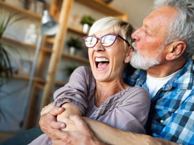 Elderly man embracing an elderly woman from behind, trying to kiss her cheeck. The woman is laughing and did not hear the man come as she has one-sided hearing loss. The man is wearing invisible hearing aids.
