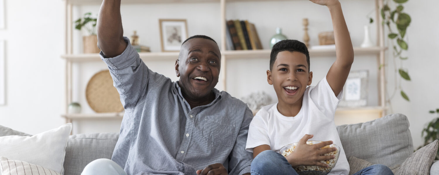 Grandfather and grandson sitting on the couch cheering after something happened on the television. The grandfather with hearing loss is using assistive devices such as hearing aids to better hear the TV.