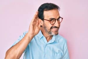 Man smiling and holding is ear asif he has one-sided hearing loss. He is considering getting invisible hearing aids.