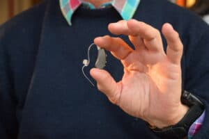 Man holding the Lexie hearing aid in in hand, thinking about hearing aid prices.
