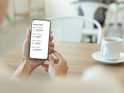 A person holding their phone while sitting at a table with coffe and scrolling through Lexie Rewards to see if they have achieved points for wearing their Lexie Lumens hearing aids.