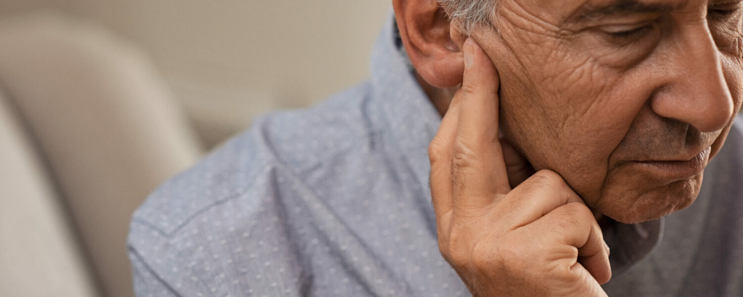 Senior man holding is ear asif he has a hearing loss, possibly due to meniere's disease symptoms and in need of a hearing aid