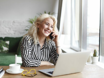 Woman sitting at a desk with her laptop open and with a cup of tea. She is speaking on the phone when she experiences sudden hearing loss