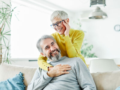 elderly couple, woman embracing the man from the back while he sits on the couch. The woman holds her ear asif she has a hearing loss in it.