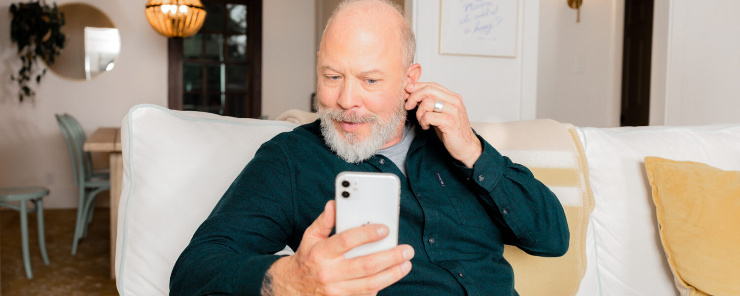 Man sitting on the couch talking with a hearing expert over the phone to send in his Lexie Lumen hearing aids for repair.