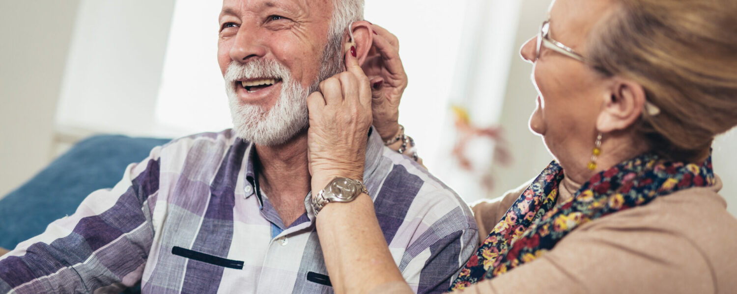 communicating with people who have a hearing loss Woman inserting over the counter hearing aids into a man's ear in their home.