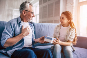 Little giving her grandfather a gift while they both sit on the couch. She followed gift ideas for hearing aid wearers to find the perfect gift.