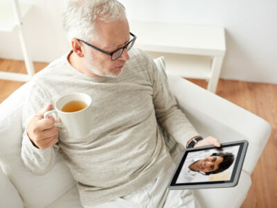 Senior man sitting on his ouch and drinking black green tea while talking with a hearing healthcare professional over is tablet after he AutoFit his hearing aids