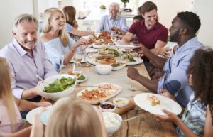 group of people around a dining table having a healthy meal discussing food and hearing health
