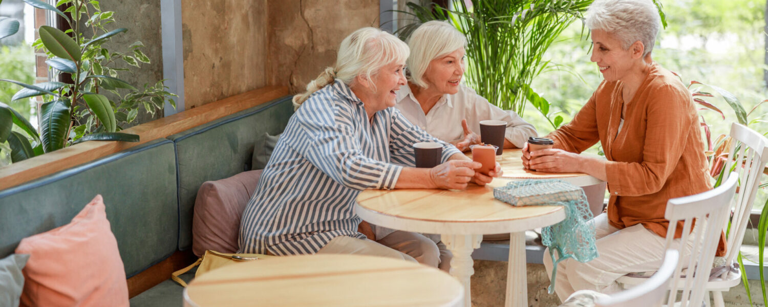 Three elderly woman sitting in a cafe having coffee while using their hearing sense to communicate with each other