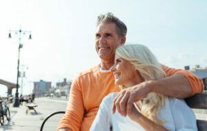 Happy senior couple spending time at the beach. Concepts about love,seniority and people. Both have hearing aid comfort