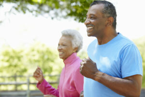 Senior African American Couple Jogging In Park, preventing their lifestyle to influence hearing
