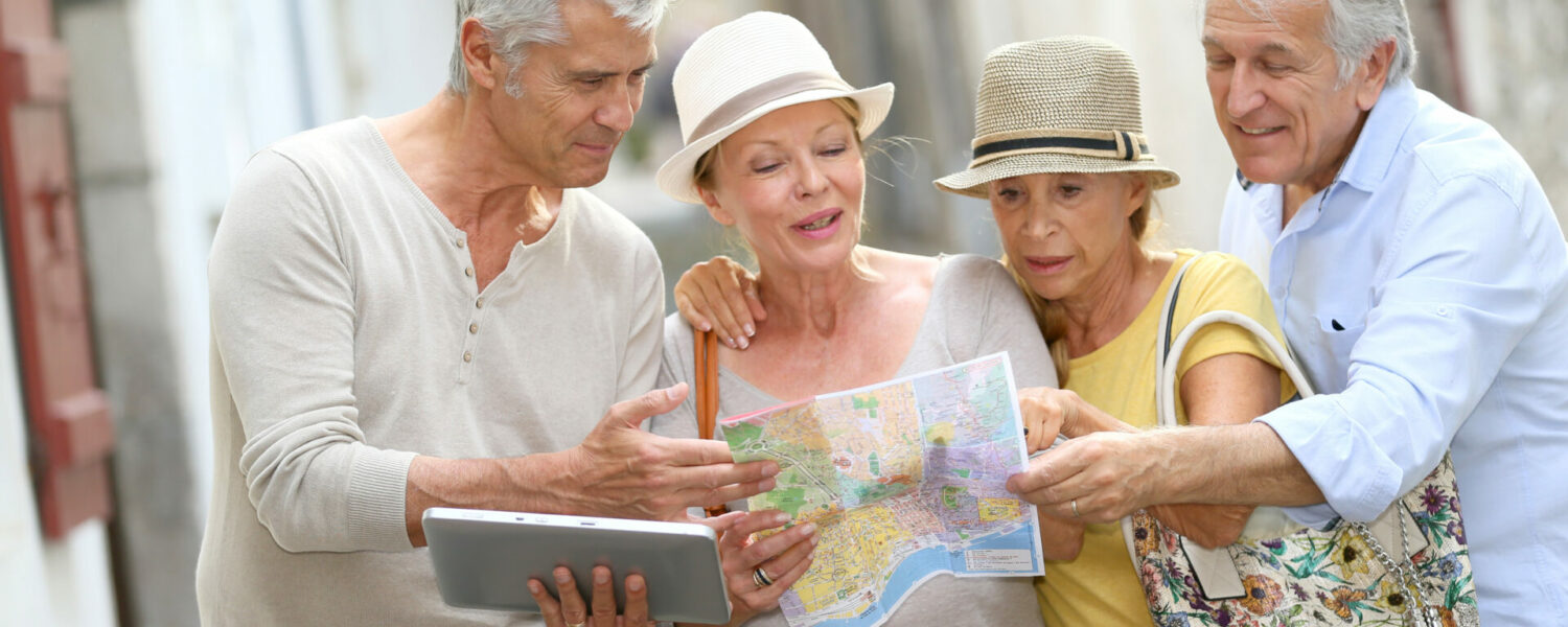 A groupd of senior people touring and using a map to move around. Their Lexie Lumen haring aids have different hearing aid channels allowing them to hear every moment clearly.