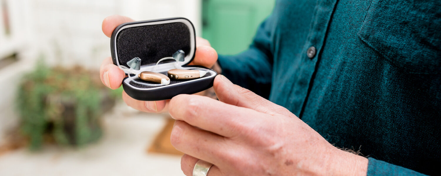 Man holding the Lexie Lumen hearing aids in their Lexie box. The Lexie Lumens are battery hearing aids that are high quality and affordable