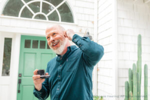 Man inserting his Lexie Lumen hearing aids because he knows the great benefit of hearing aids