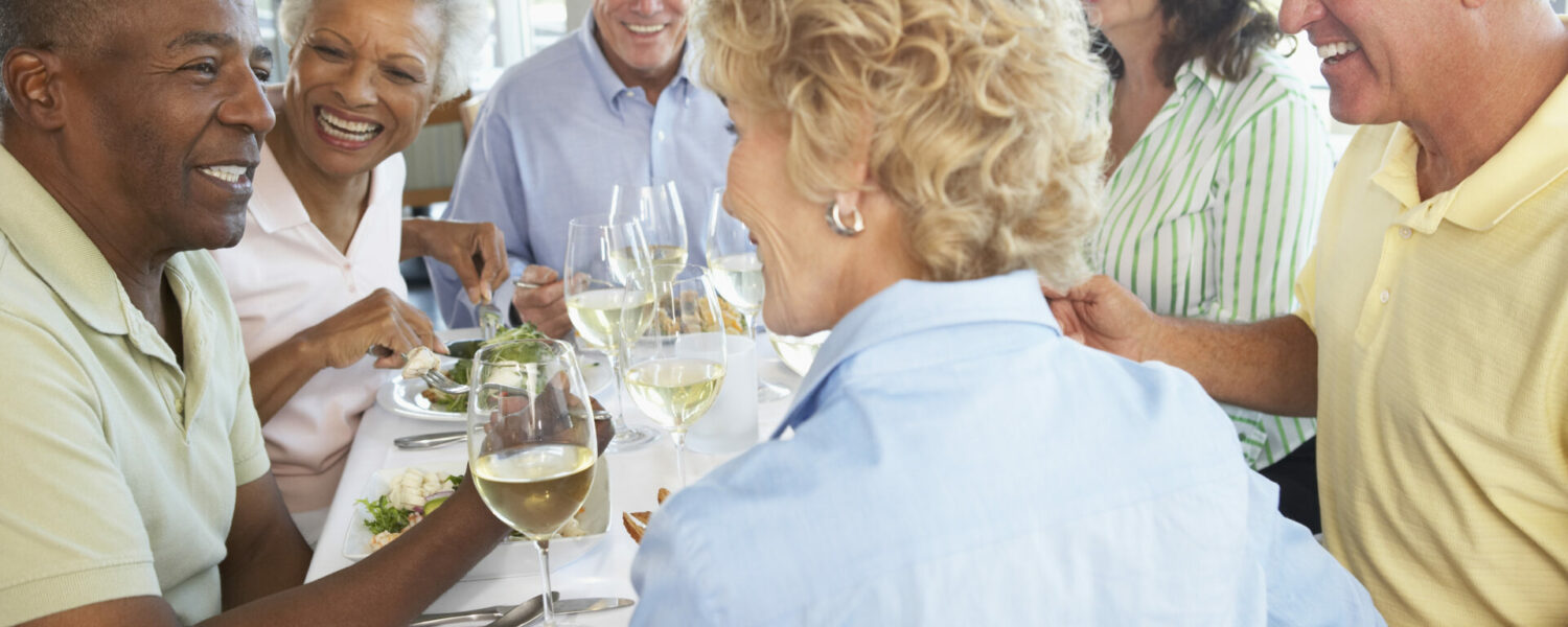 a group of elderly friends sitting in a restaurant having a meal while a woman is hearing a hearing aid and their discussing noise reduction in hearing aids