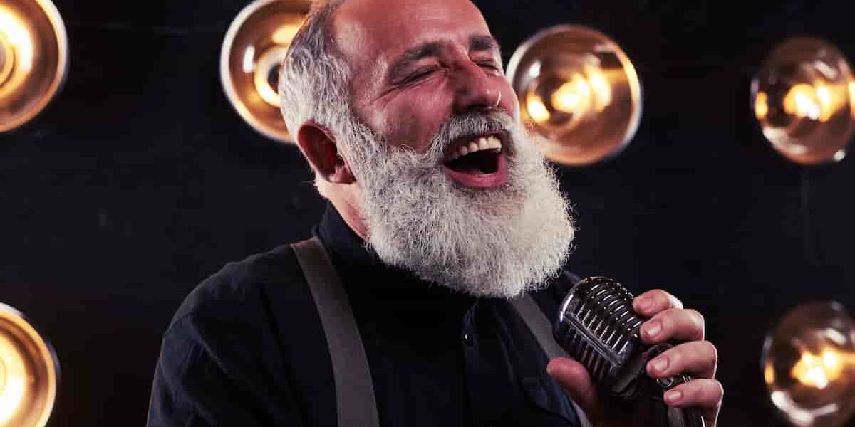 Elderly man siging into a microphone, he is singing with hearing aids