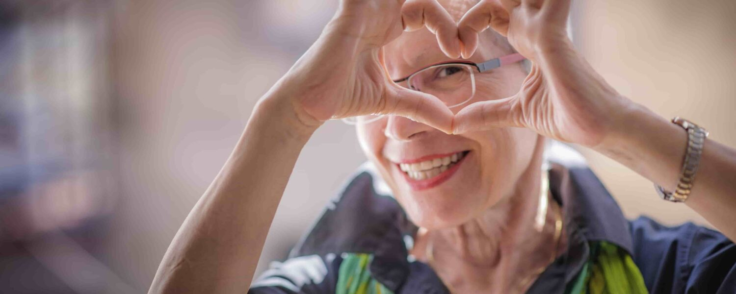 Cute senior old woman making a heart shape with her hands and fingers after gifting her old hearing aids