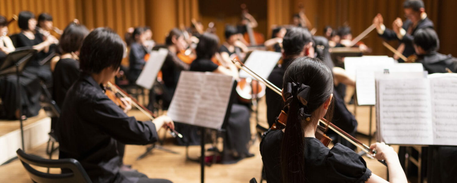A group of people, dressed in black on a stage playing a symphony, each of them wearing musician earplugs to protect their hearing.