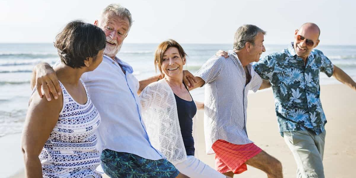 Group of older frienda embraxing each other on the beach, happy that hearing aids are fashionable