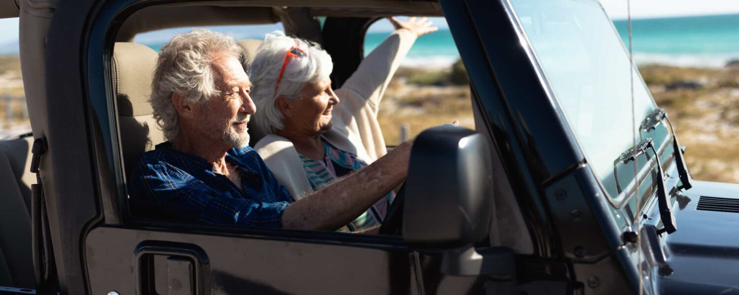 Man and woman driving in a car along the beach while listening to loud music