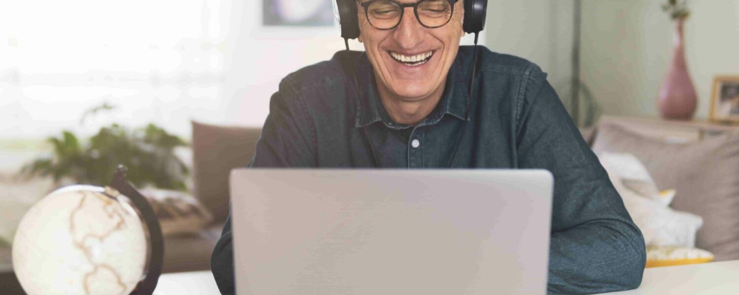 man sitting at his laptop with headphones on to take an online hearing test