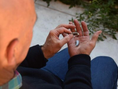 Elderly man sitting and holding directional hearing aids in his hands