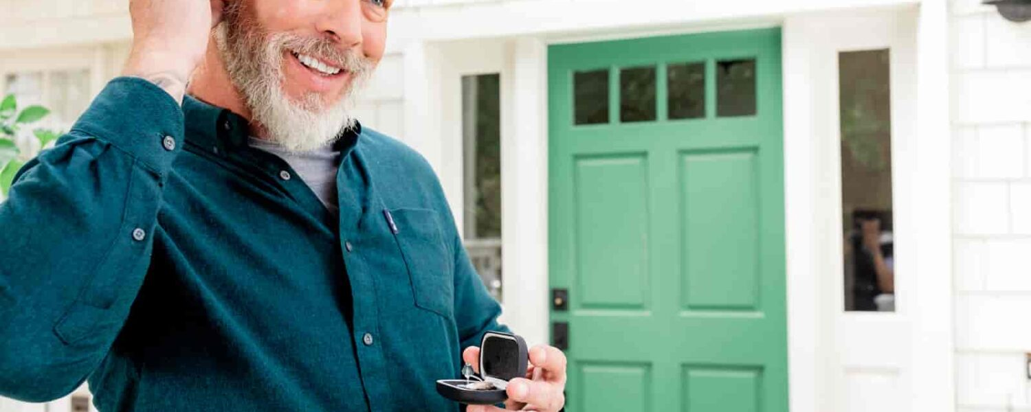Handsome elderly man inserting his slim and sleek Lexie Lumen hearing aids while breaking the stigma of hearing aids