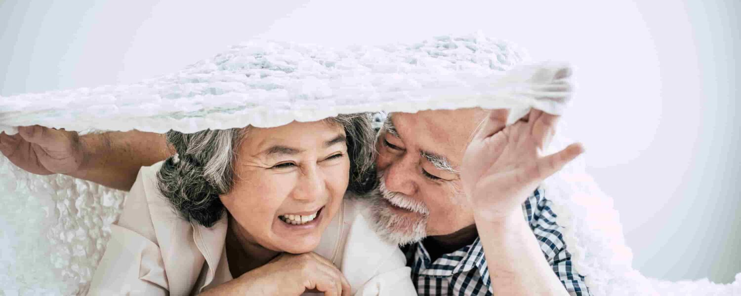 Man and woman laying in bed laughing and discussing rechargeable hearing aids