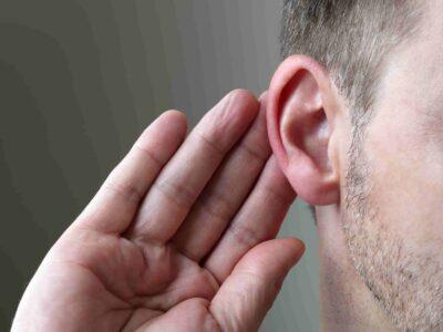 Vestibular System. Man holding is hand to his ear.