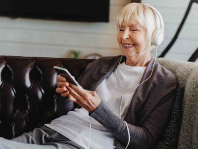 Senoir woman on the couch with headphones. Headphones and hearing loss