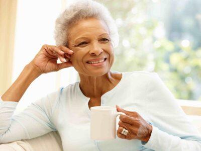 A senior woman drinking tea, thinking of healing hearing loss