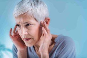Woman holding her ears as they are hurting. Why are my ears ringing?