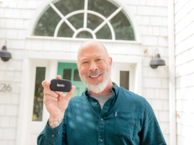 Man holding Lexie hearing aids showing how to use hearing aids
