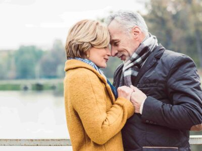 Happy couple next to the lake during winter trauma and hearing loss