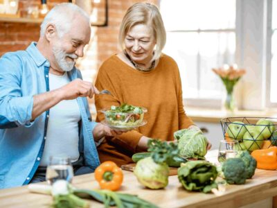 Senior man and woman in the kitchen cooking a meal to get all their vitamins for ear health