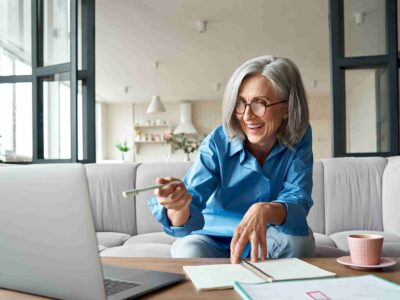 Senior woman working on her laptop searching for how much do hearing aids cost